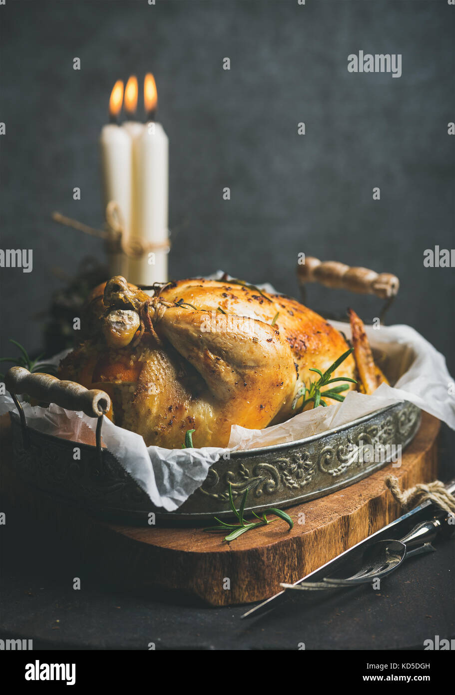 Christmas holiday table set with roasted whole chicken and candles - Stock Image