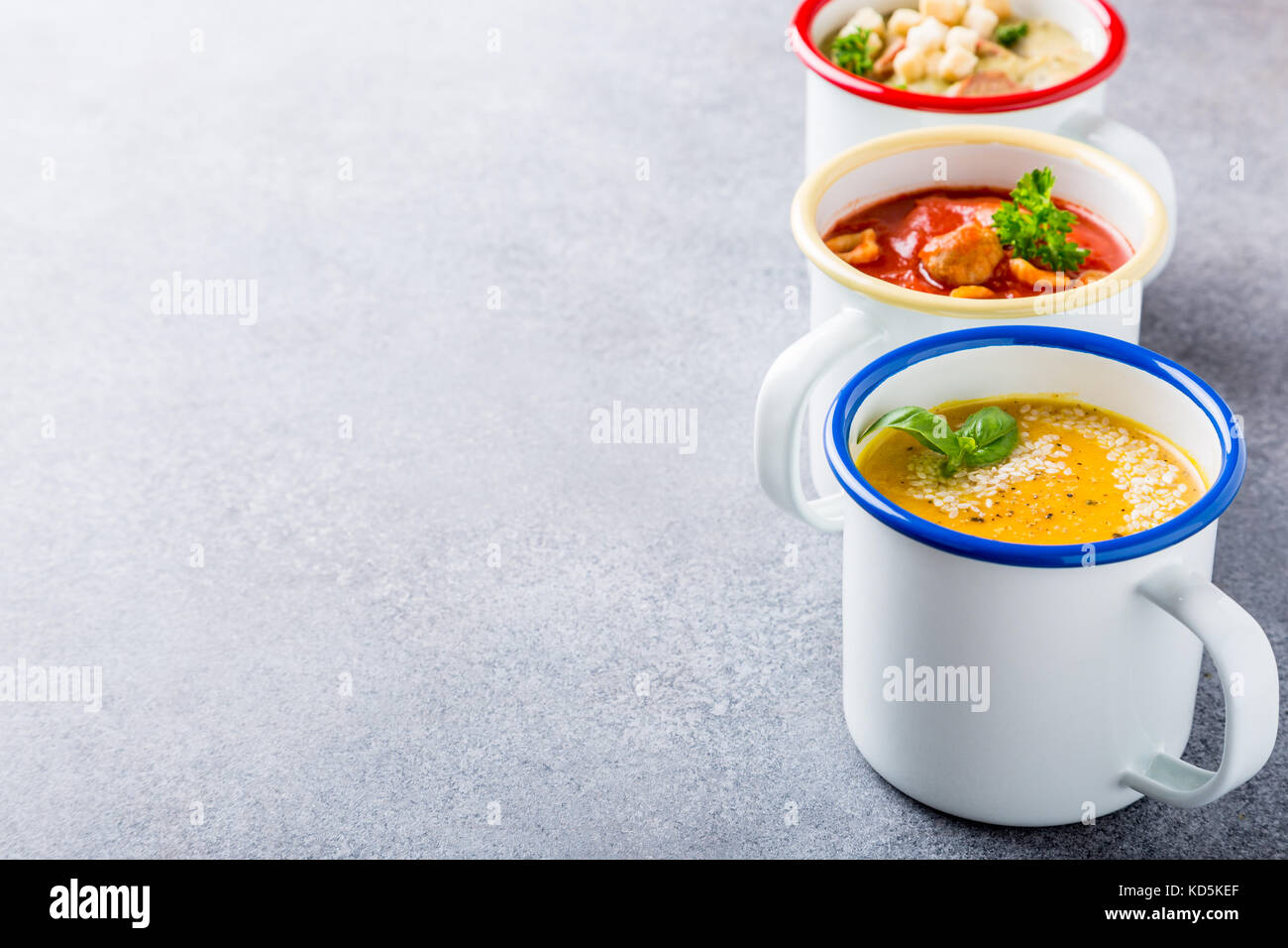 Assorted delicious homemade soups in enamel mugs with ingredients. Healthy food concept with copy space. - Stock Image