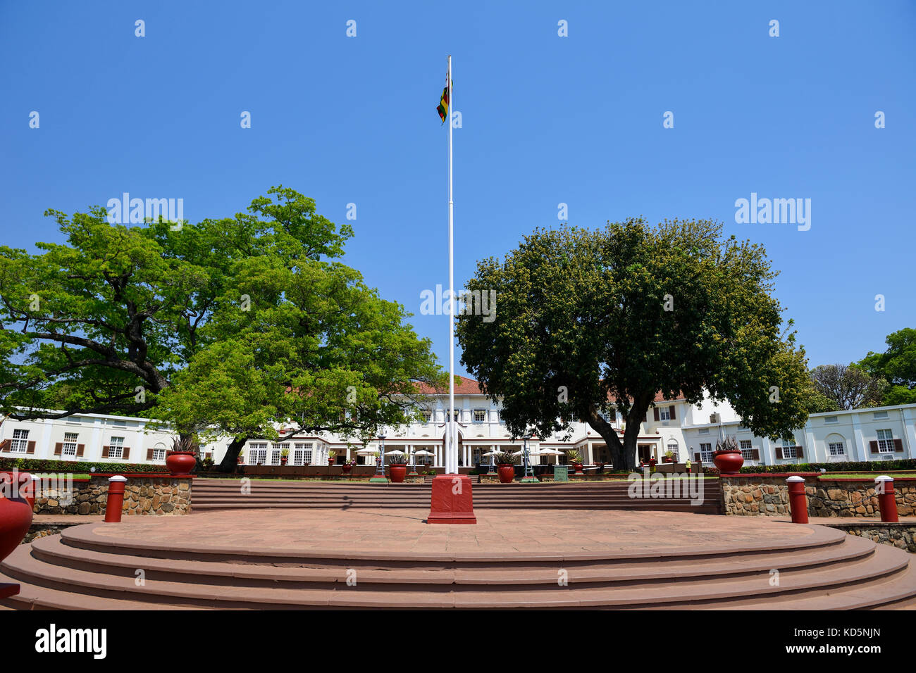 Flagpole flying Zimbabwean flag in garden of Victoria Falls Hotel, Victoria Falls, Zimbabwe, Southern Africa Stock Photo