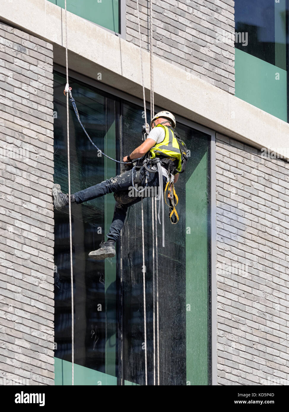 LONDON:  Builder working on Windows of Tall Office Building using safety Equipment - Stock Image