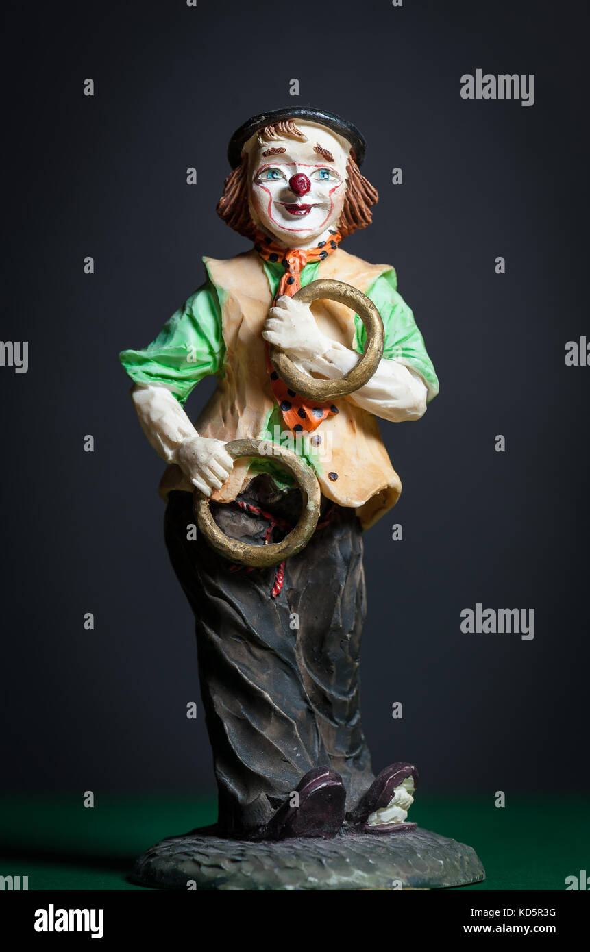 Closeup of a small figurine of a juggling clown with rings - Stock Image