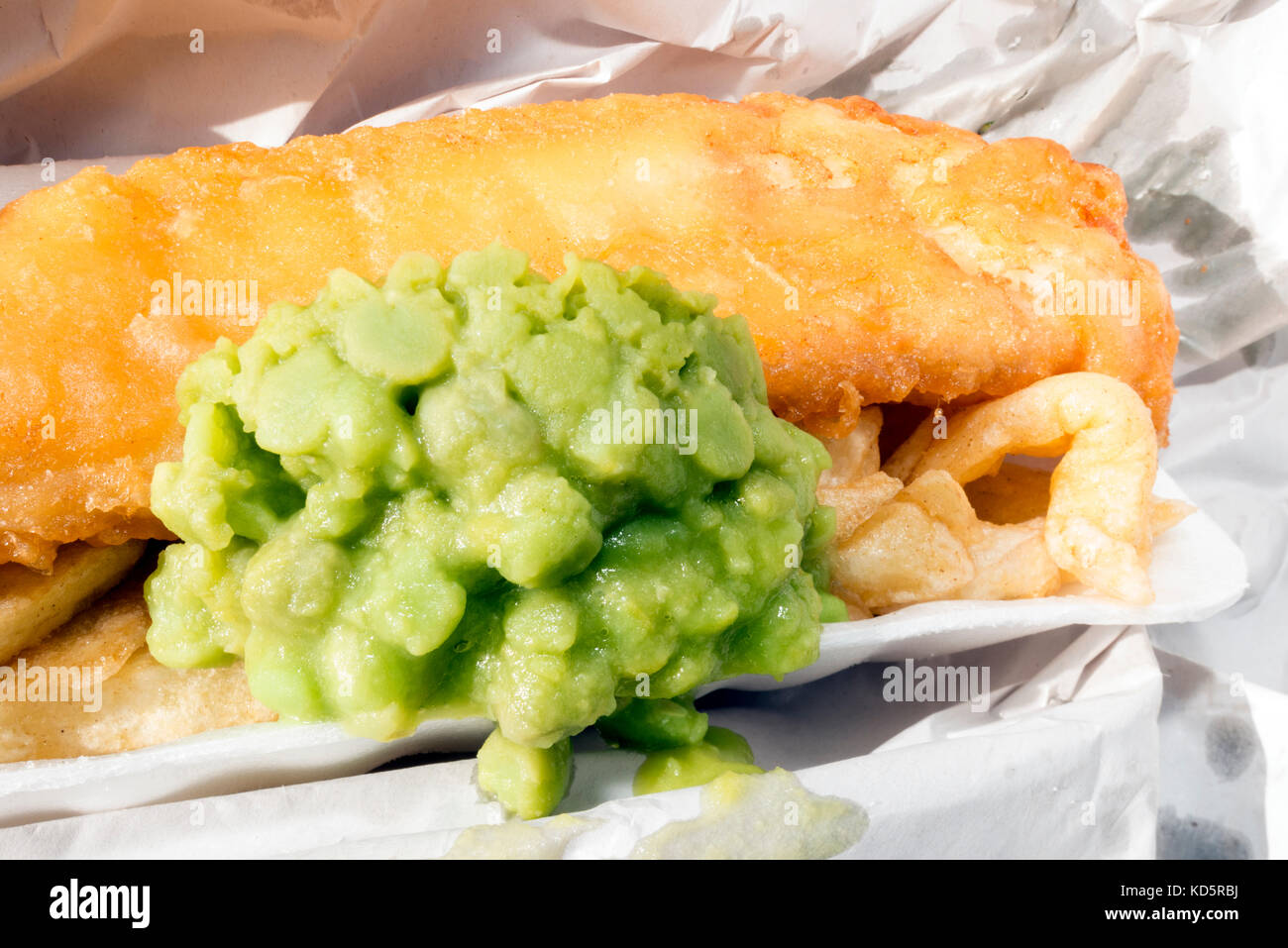 Fish and chips with mushy peas, wrapped in paper from a takeaway, UK. - Stock Image