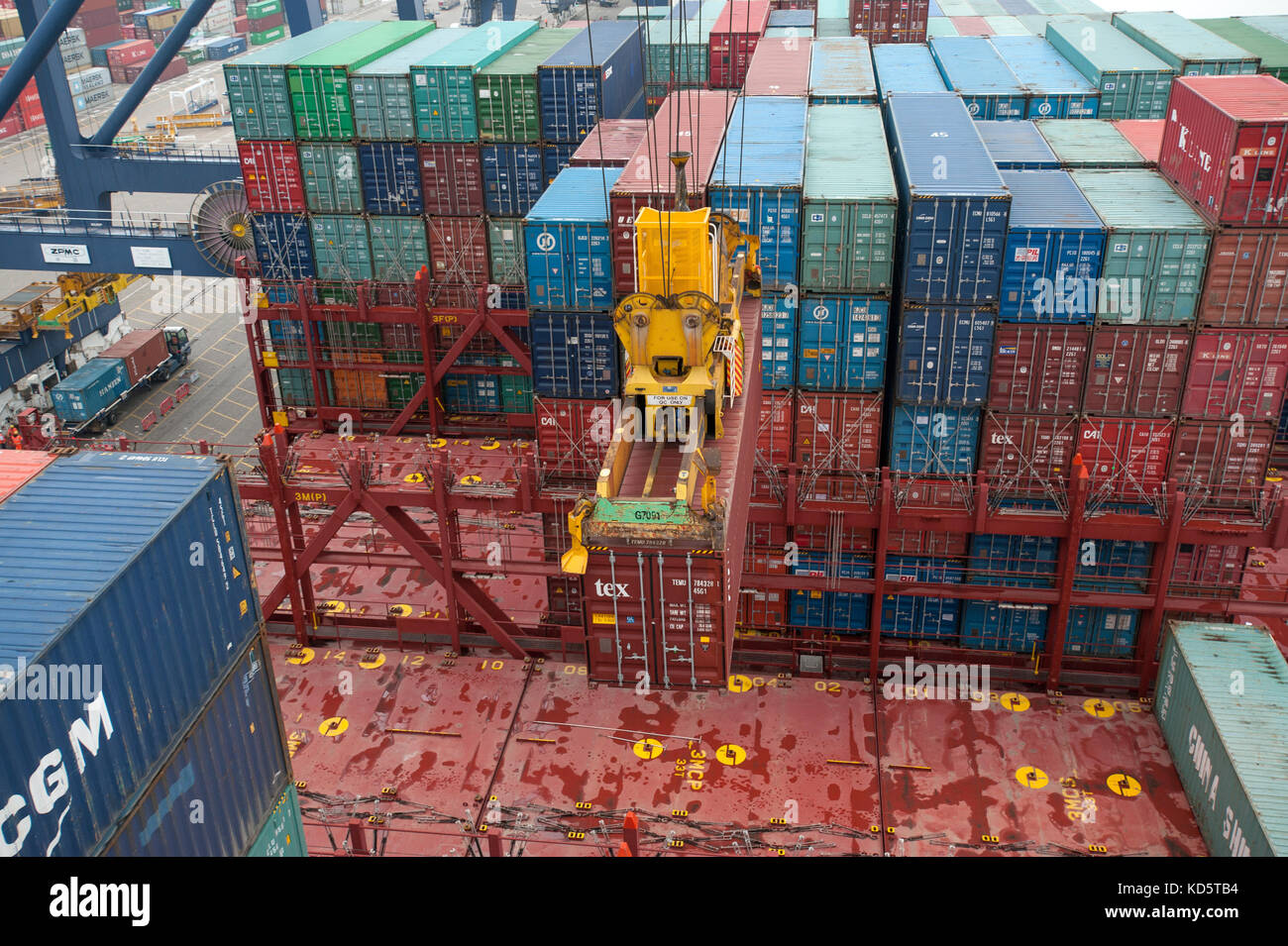 Shipping containers in container port and on-board ship - Stock Image