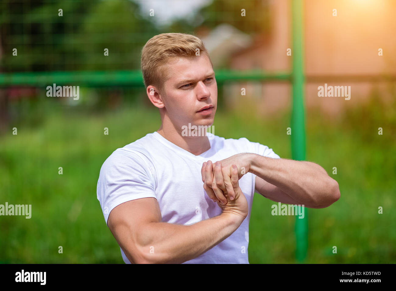 Stretches the muscles of the teams. The coach man does the warm-up, in the city on the nature, in the summer in - Stock Image