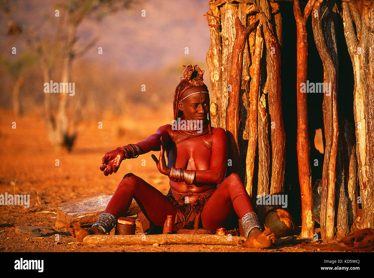 Namibia. Kunene region. Himba woman sitting under tree. - Stock Image