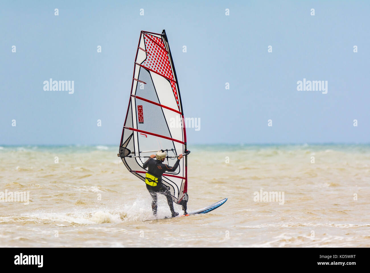 Windsurfer on the sea on a windy day in the UK. - Stock Image