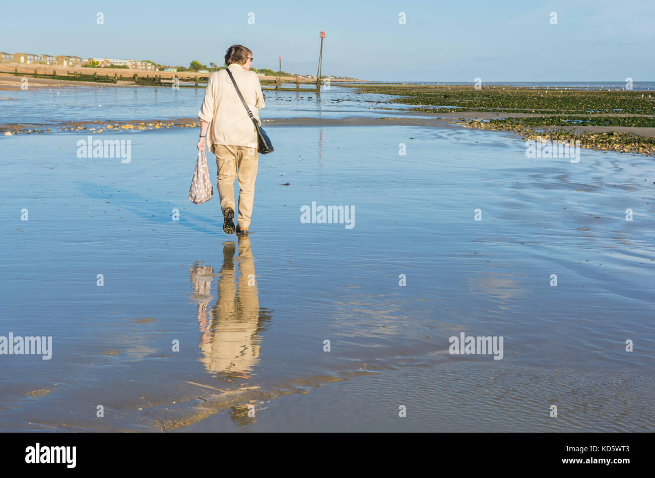 Woman waking on a beach at low tide with a reflection of her in the wet sand. - Stock Image