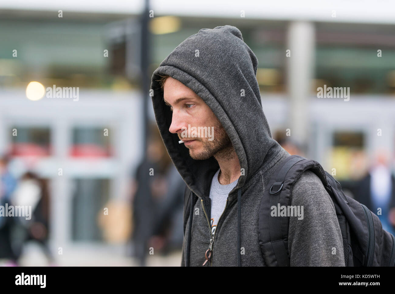 Young man in a city wearing a hoody with the hood up, in the UK. - Stock Image