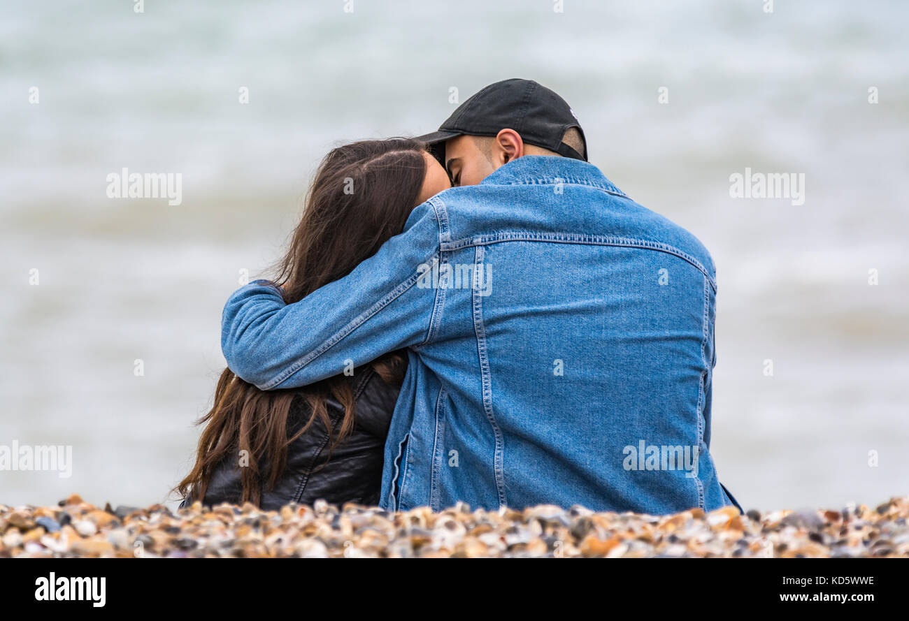 Young couple sitting on a beach kissing and embracing each other. Young lovers hugging on the beach. Stock Photo