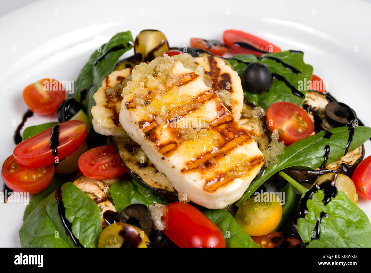 Grilled Halloumi Cheese poured with garlic olive oil salad witch grilled eggplant, cherry tomatoes, black olives Stock Photo