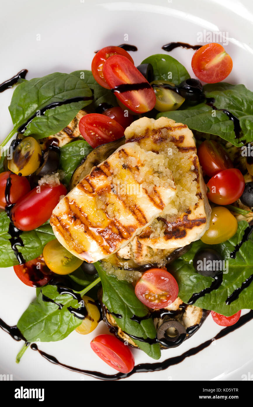 Grilled Halloumi Cheese poured with garlic olive oil salad witch grilled eggplant, cherry tomatoes, black olives - Stock Image