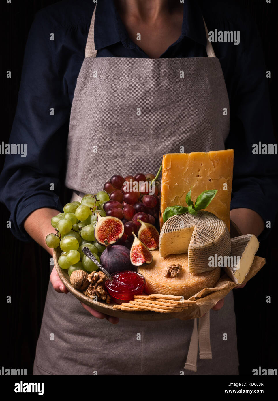 Woman holding a cheese plate with fruits and jam - Stock Image