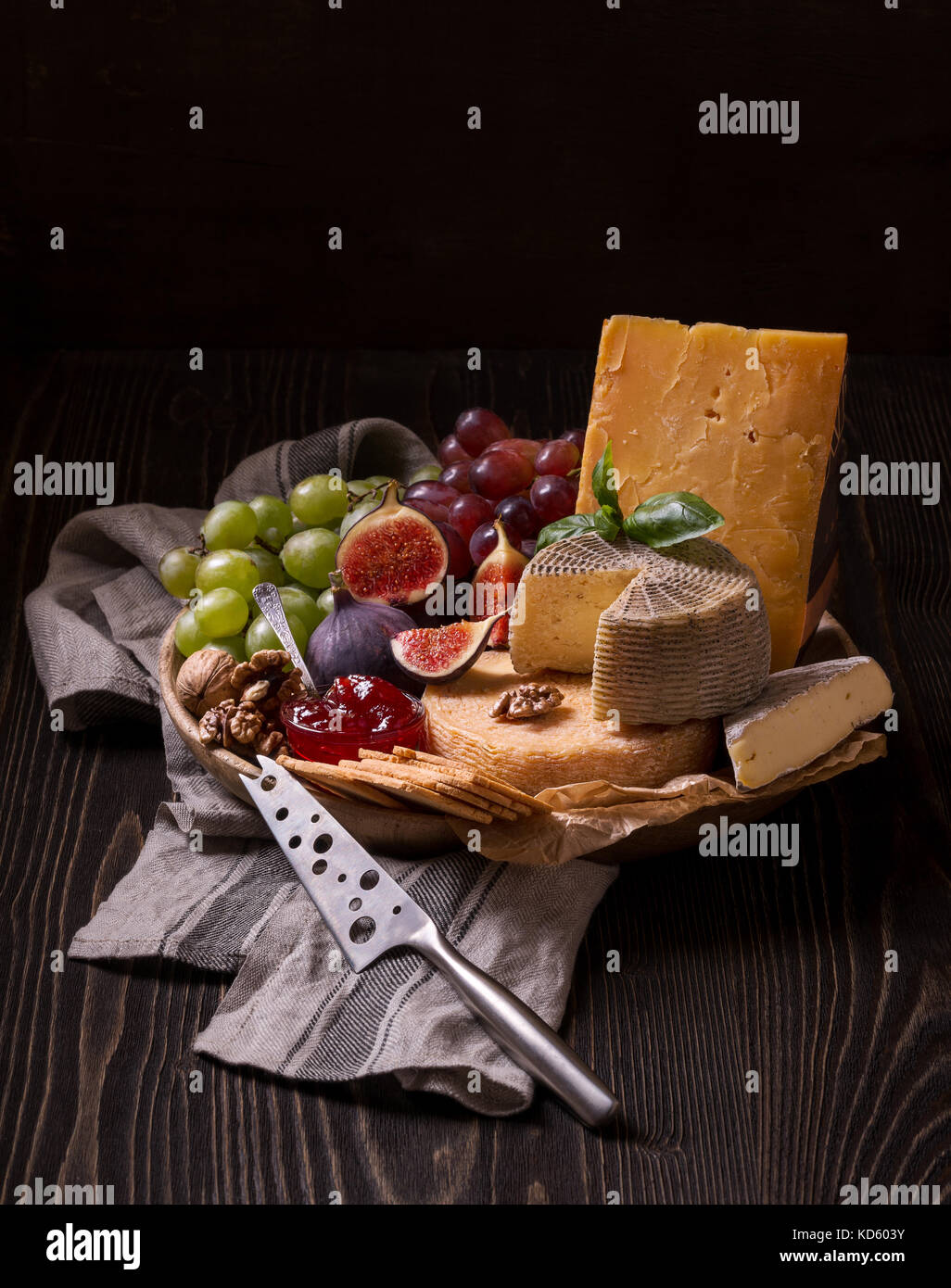 Cheese platter on the rough wood - Stock Image