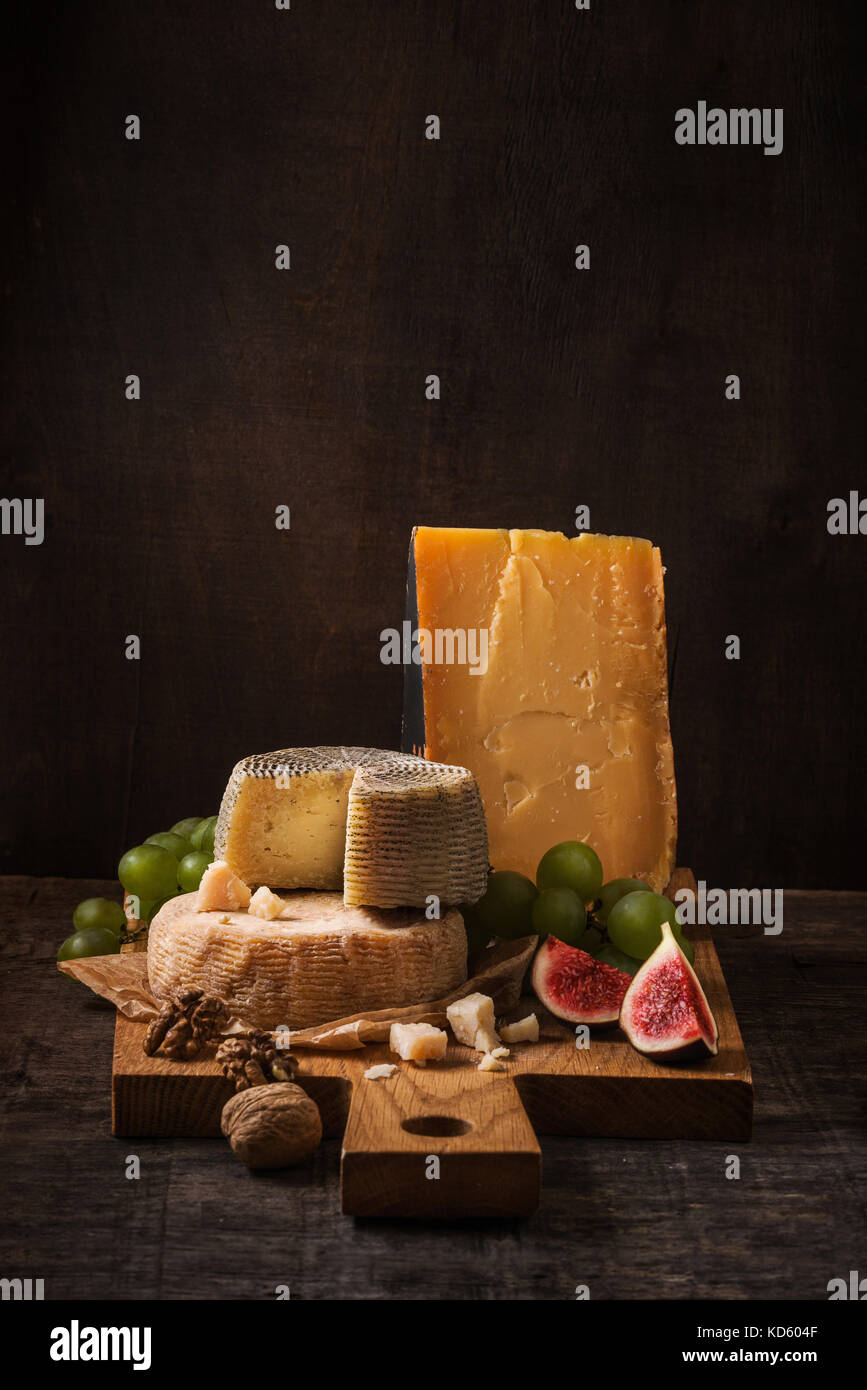 Cheese board, fruits and nuts on the rough wood - Stock Image