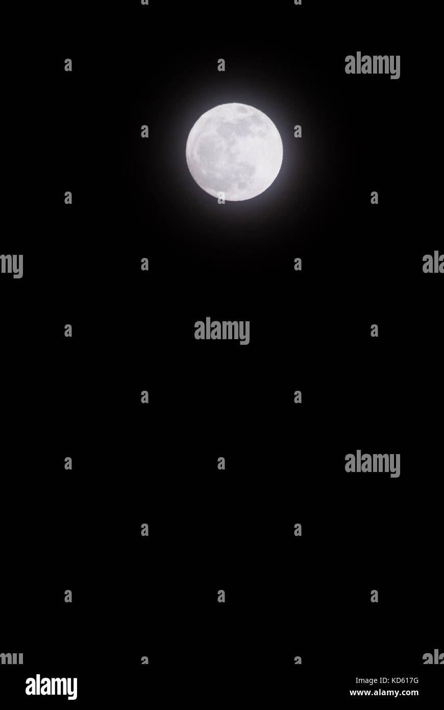 Full Moon and a Black Sky. A full moon shines in a totally dark sky at night. - Stock Image