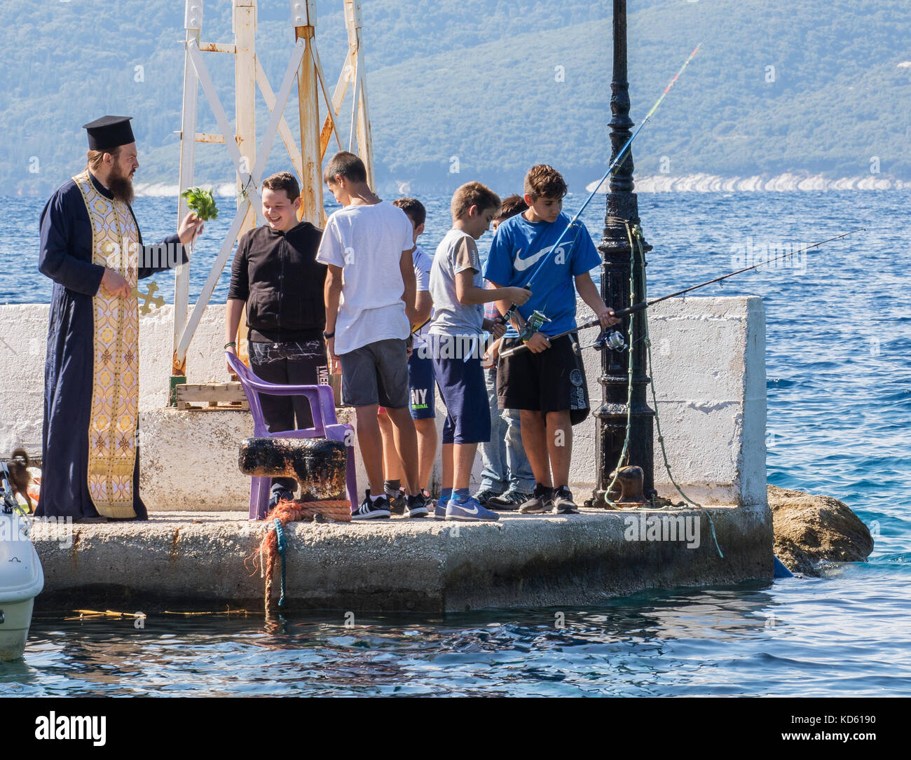 Priest blessing the catch as local boys fish at a fishing festival in Polis harbour near the village of Stavros Stock Photo