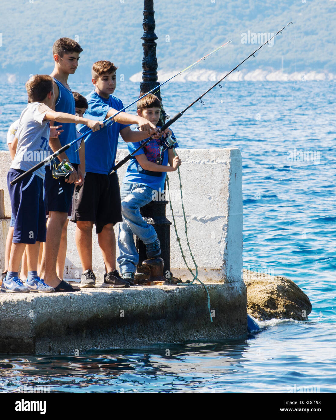 Local boys fishing off the end of a jetty at a fishing festival in Polis harbour near the village of Stavros on Stock Photo