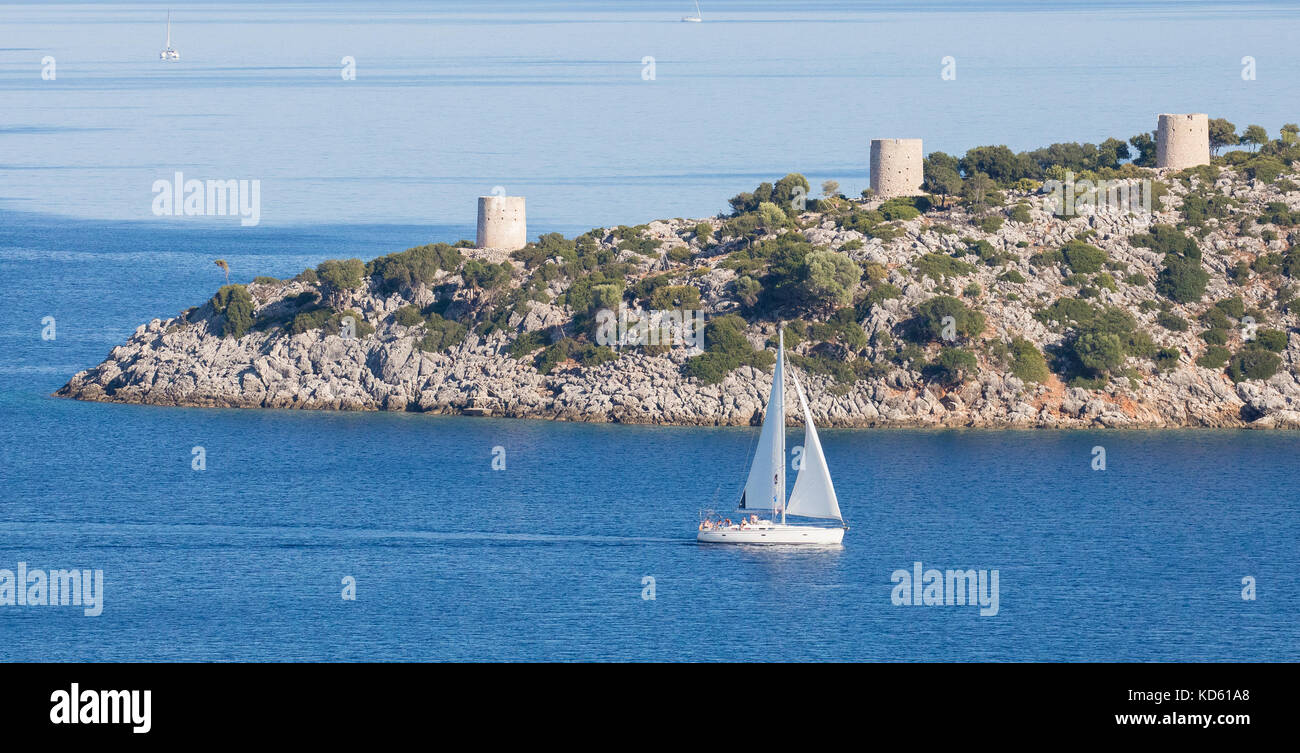 Yacht sailing by the three windmill towers at the entrance to Kioni harbour on the island of Ithaka in the Ionian - Stock Image