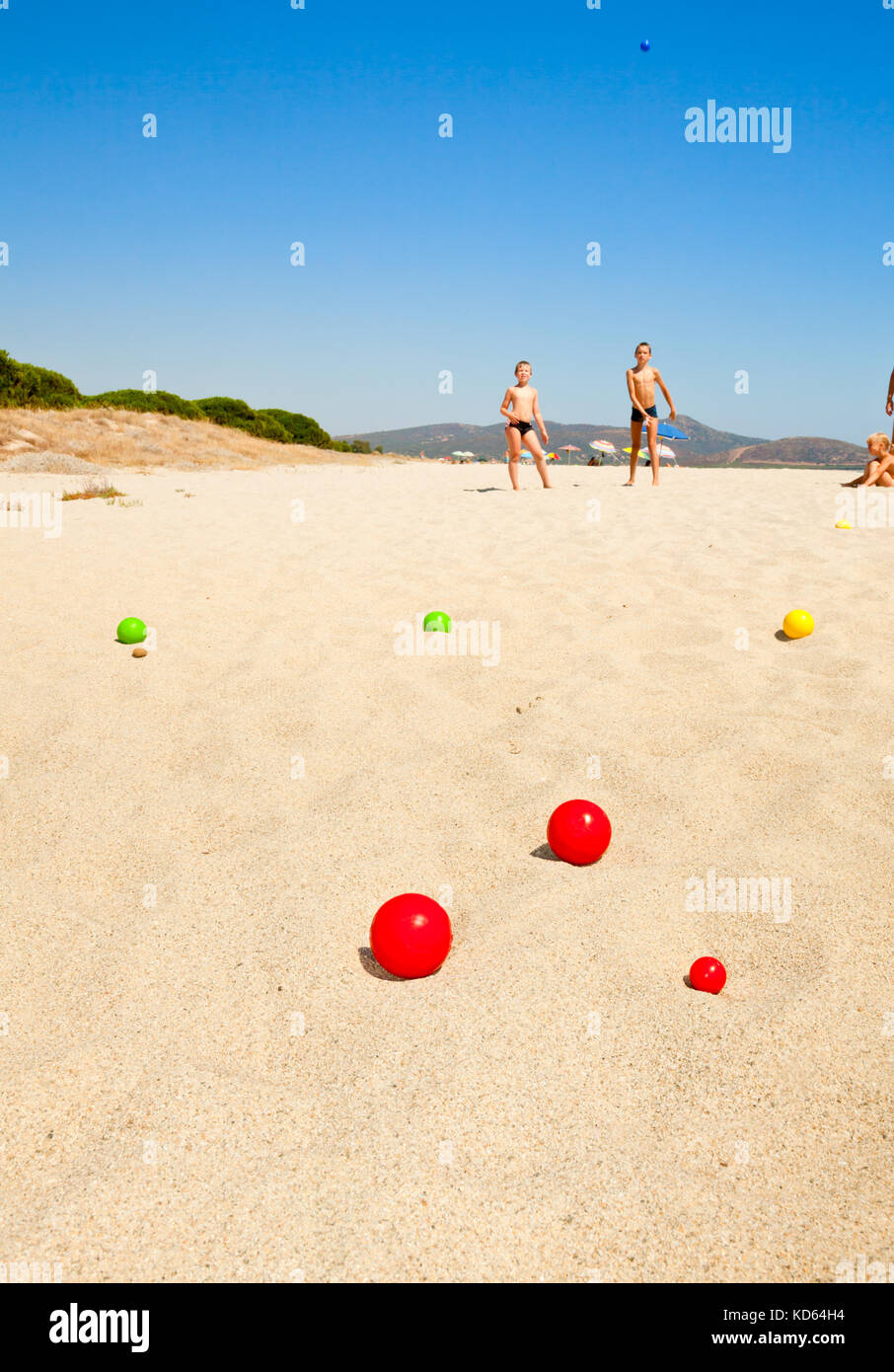 Boys playing petanque on a beach, focus on balls - Stock Image
