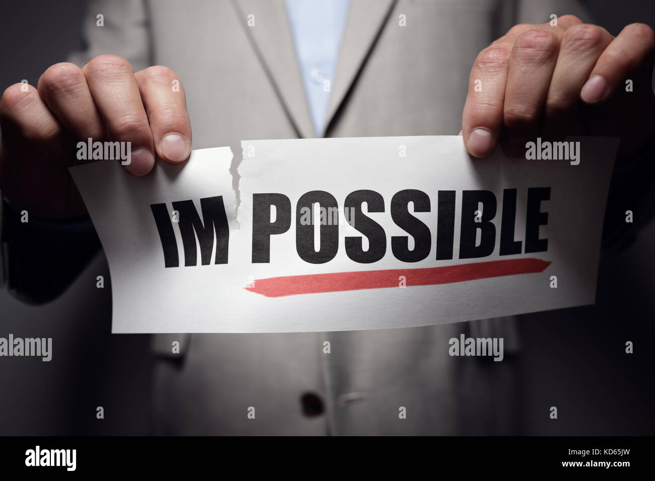 Businessman tearing the word impossible to make possibe concept for self belief, positive attitude and  motivation - Stock Image