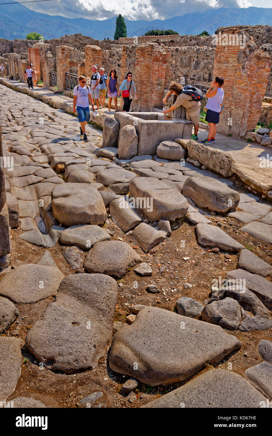 Street with communal water font in the ruined Roman city of Pompeii at Pompei Scavi, near Naples, Southern Italy. Stock Photo