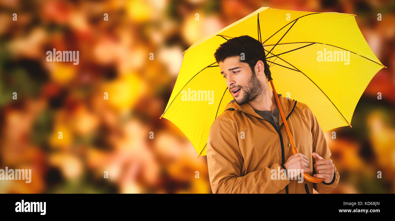 Young man holding yellow umbrella against maple leaves fallen on grass - Stock Image
