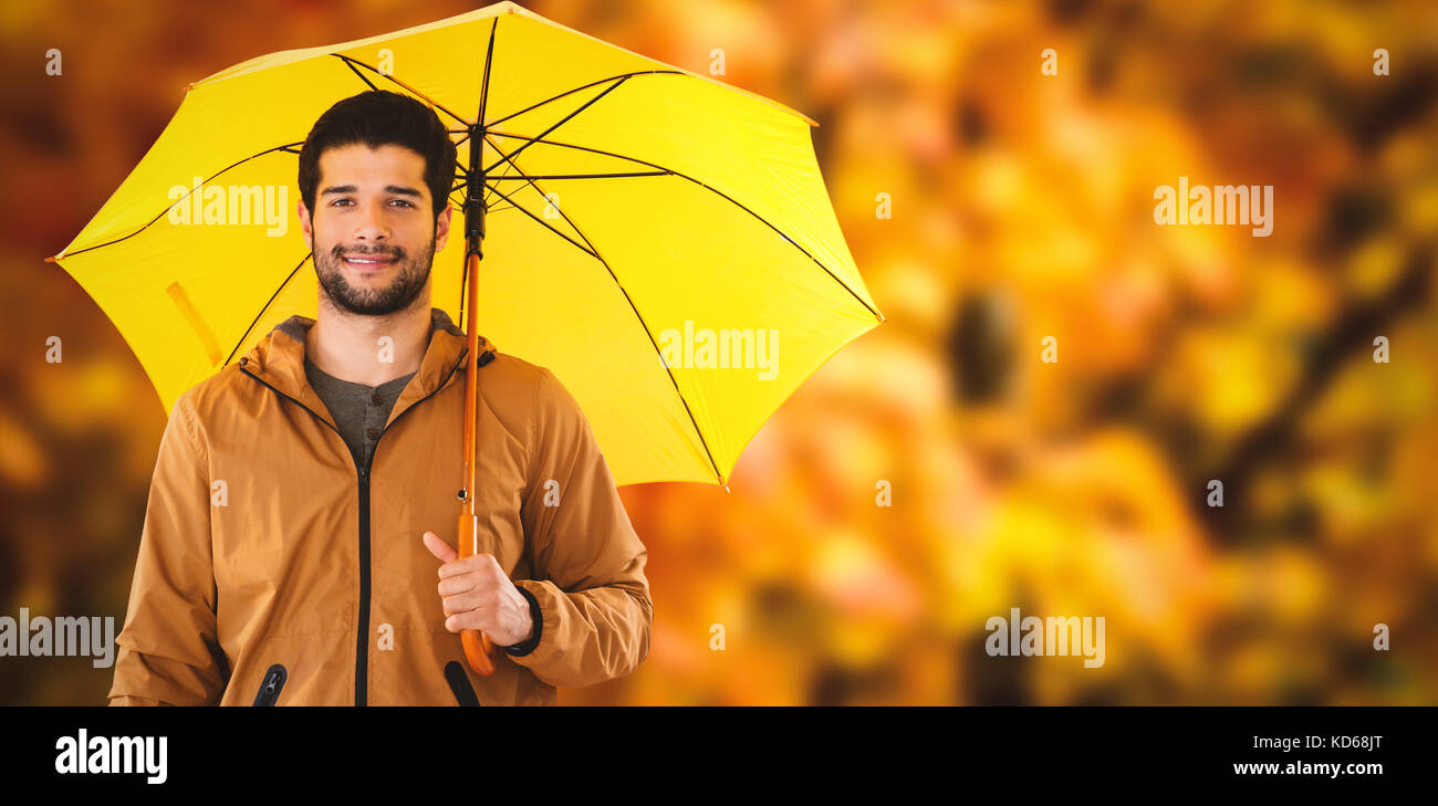 Portrait of young man holding yellow umbrella against low angle view of maple leaves - Stock Image