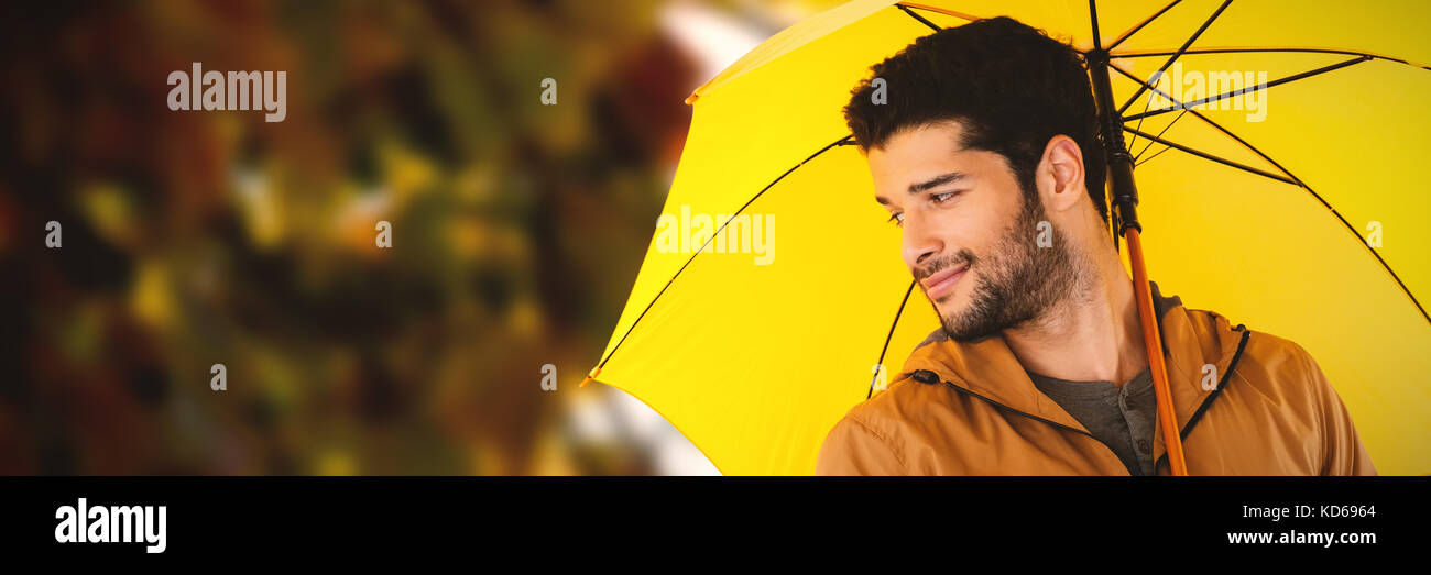 Smiling man holding yellow umbrella against view of maple leaves - Stock Image