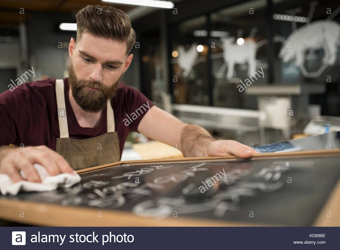 Focused male butcher writing prices on blackboard in butcher - Stock Image