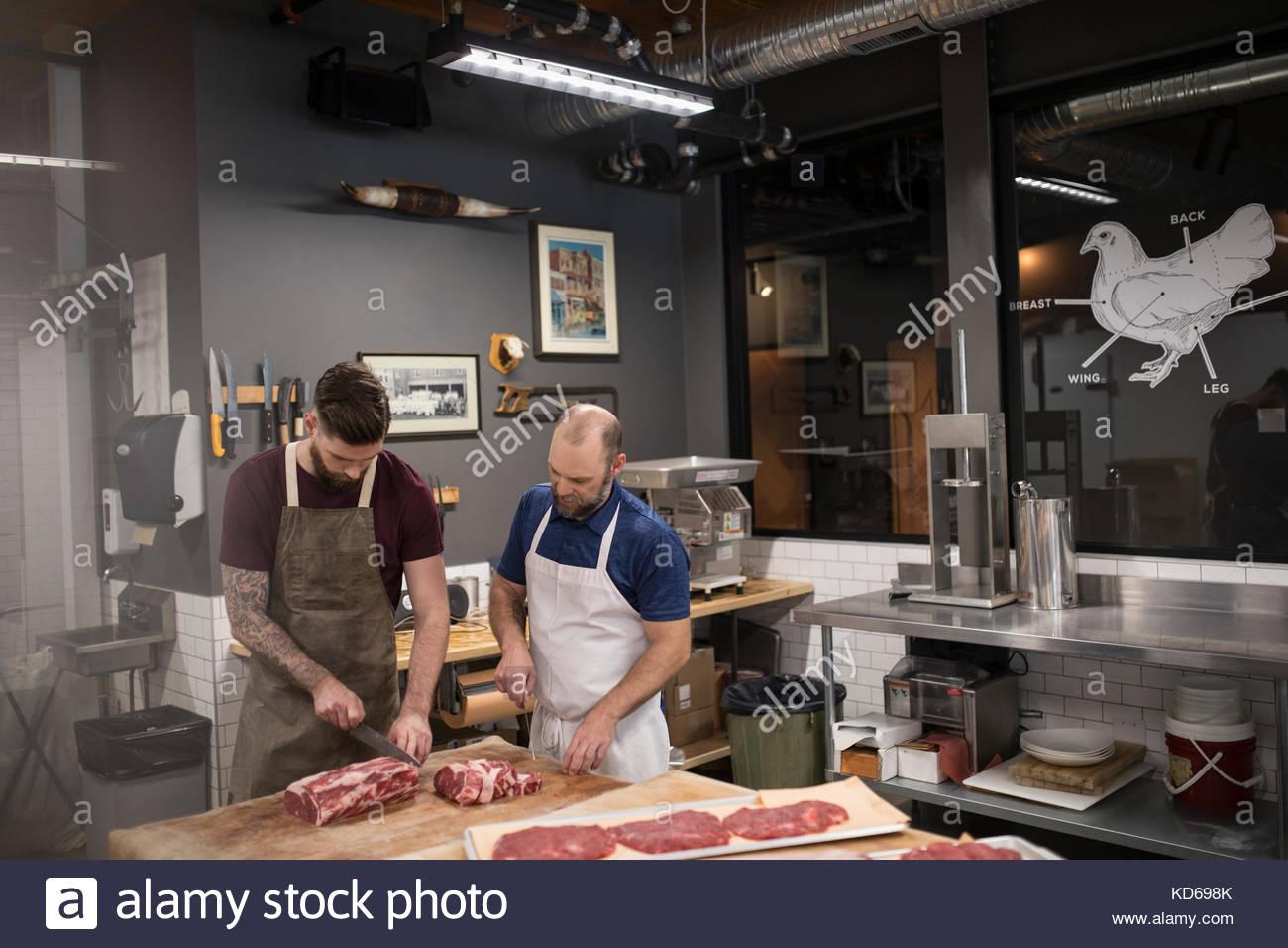 Male butchers cutting raw red meat in butcher - Stock Image