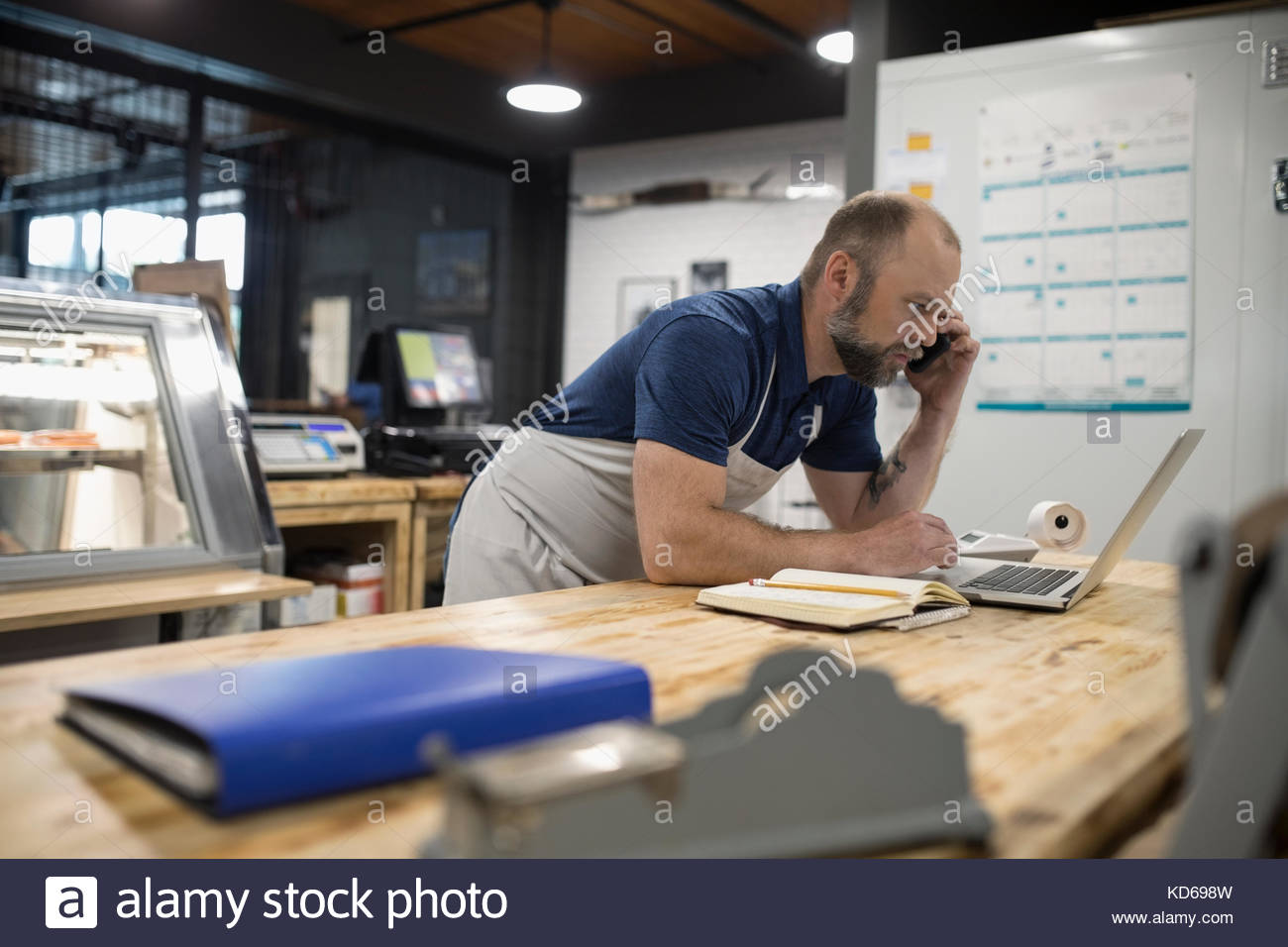 Male butcher paying bills, working at laptop and talking on cell phone in butcher - Stock Image