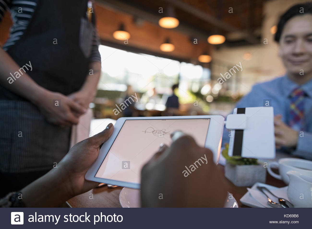 Female customer paying, signing digital tablet credit card swiper at restaurant table - Stock Image