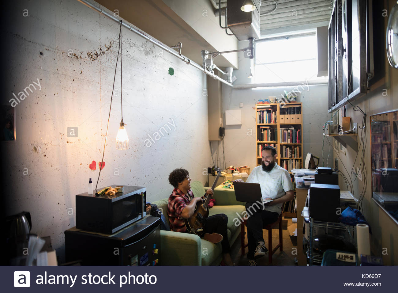 Musicians playing guitar, using laptop in apartment - Stock Image