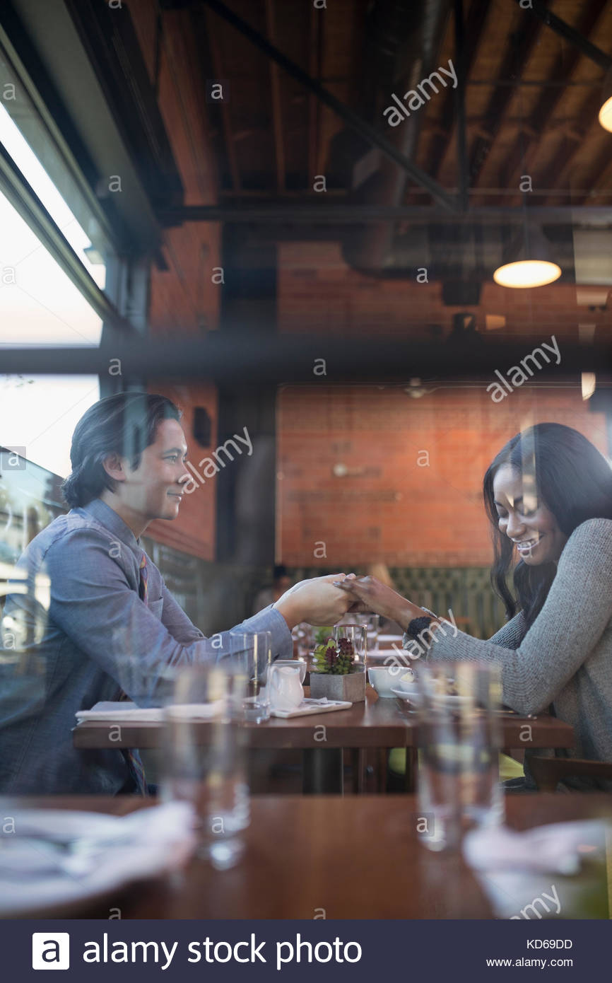 Affectionate couple holding hands, dining at restaurant table - Stock Image