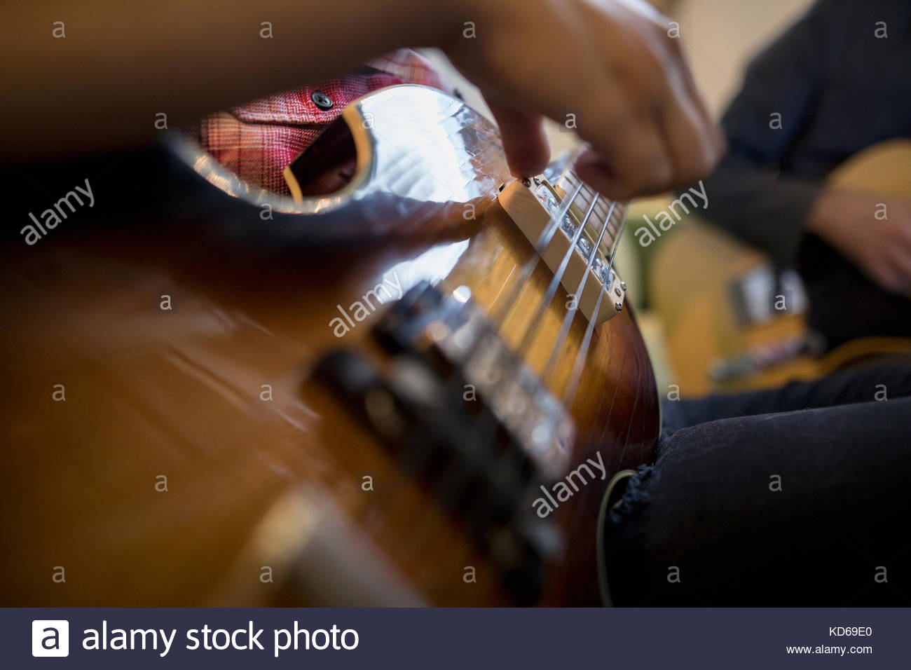 Close up musician strumming guitar - Stock Image
