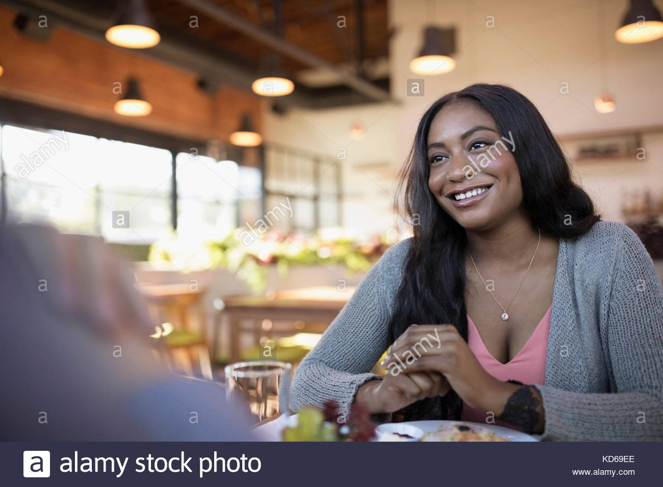 Smiling woman dining at restaurant table - Stock Image