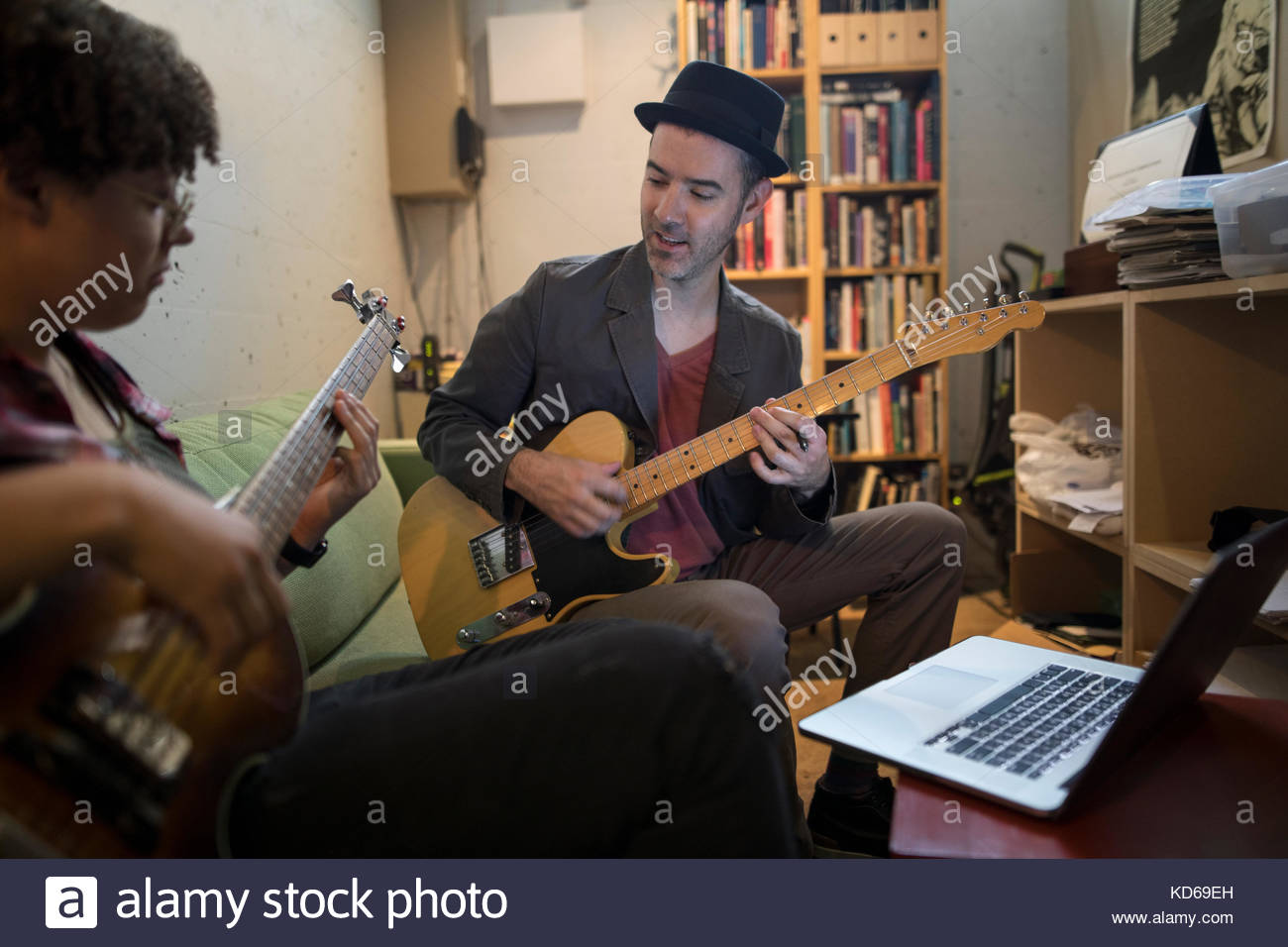 Musicians playing guitars at laptop in apartment - Stock Image