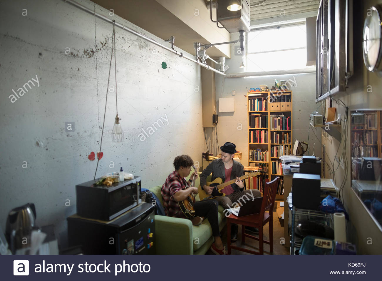 Musicians playing guitars in apartment - Stock Image