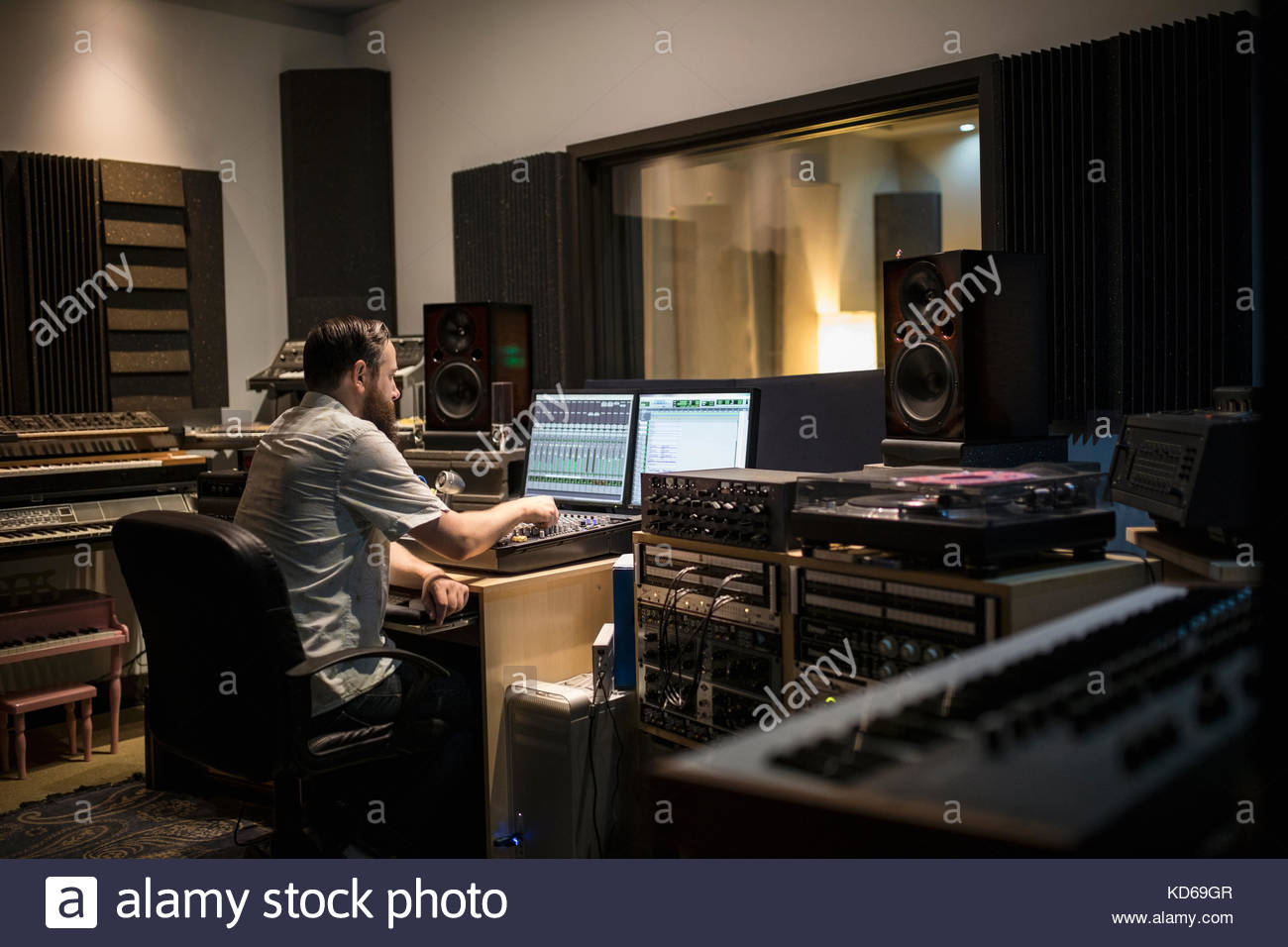 Male music producer working at computer in recording studio - Stock Image