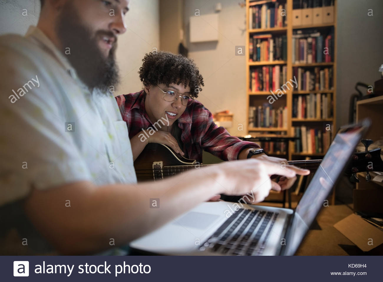 Musicians with guitar writing music at laptop - Stock Image