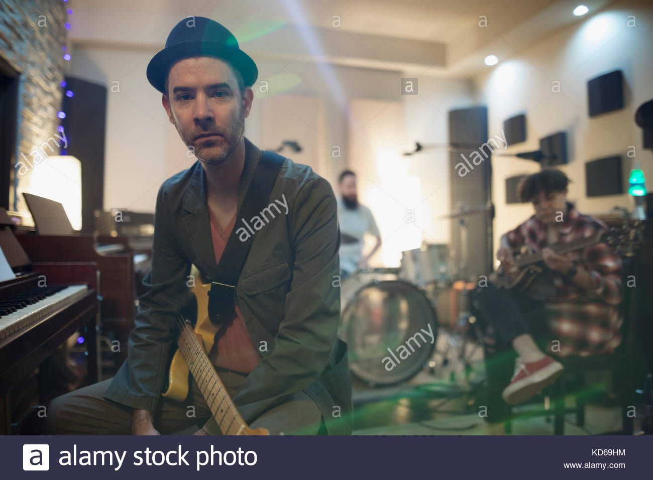 Portrait serious, confident musician with guitar sitting at piano in recording studio - Stock Image