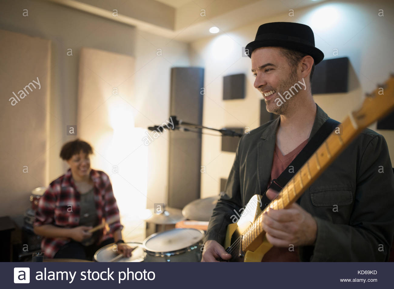Smiling male guitarist playing in recording studio - Stock Image