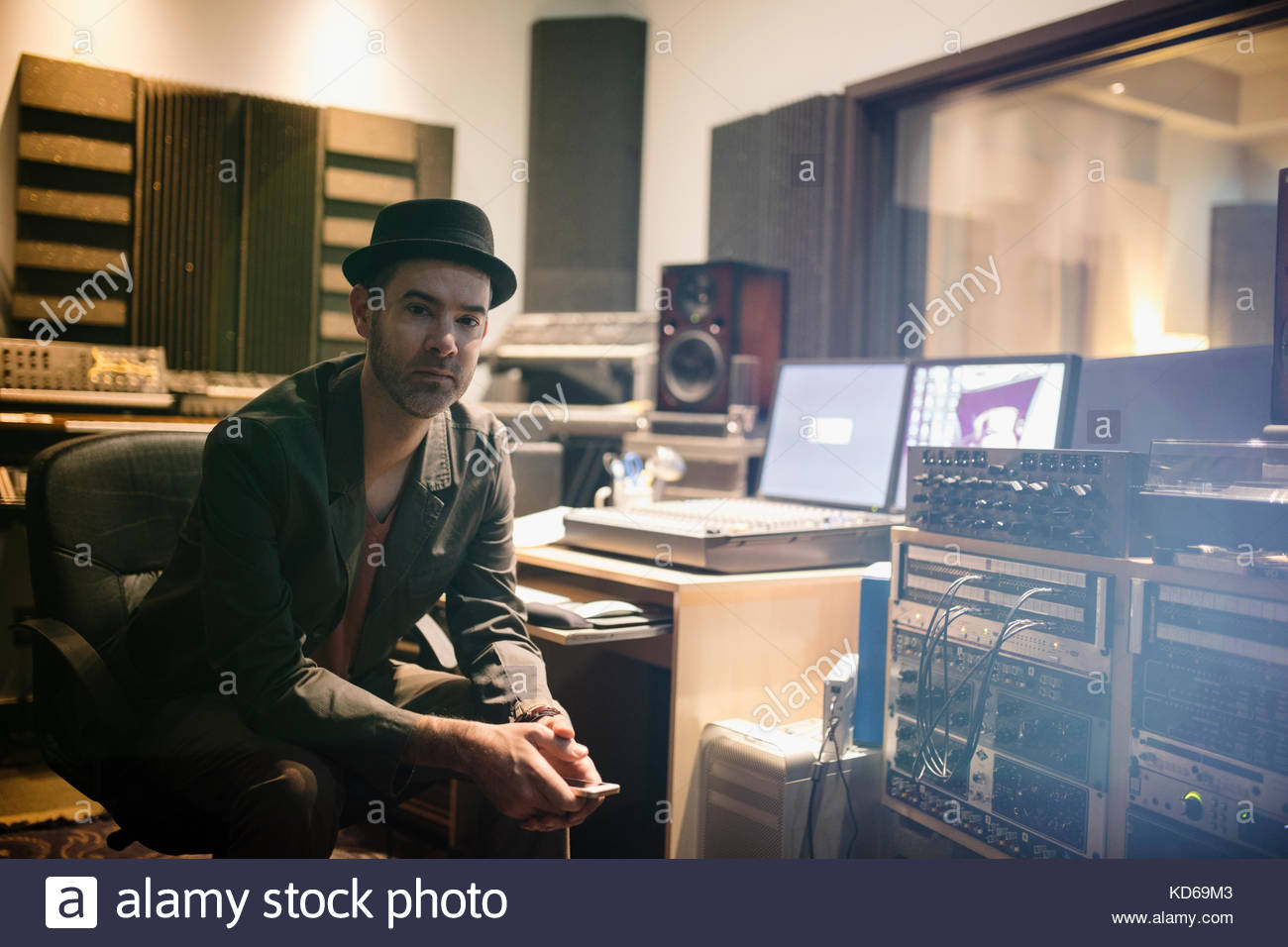 Portrait confident male musician texting with cell phone in recording studio - Stock Image