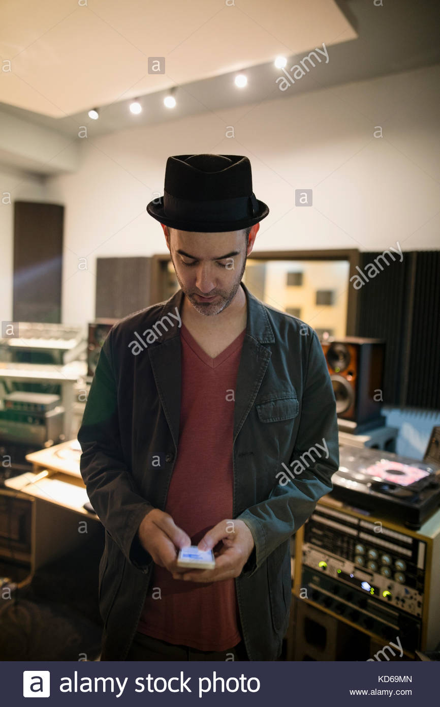 Male musician texting with cell phone in recording studio - Stock Image