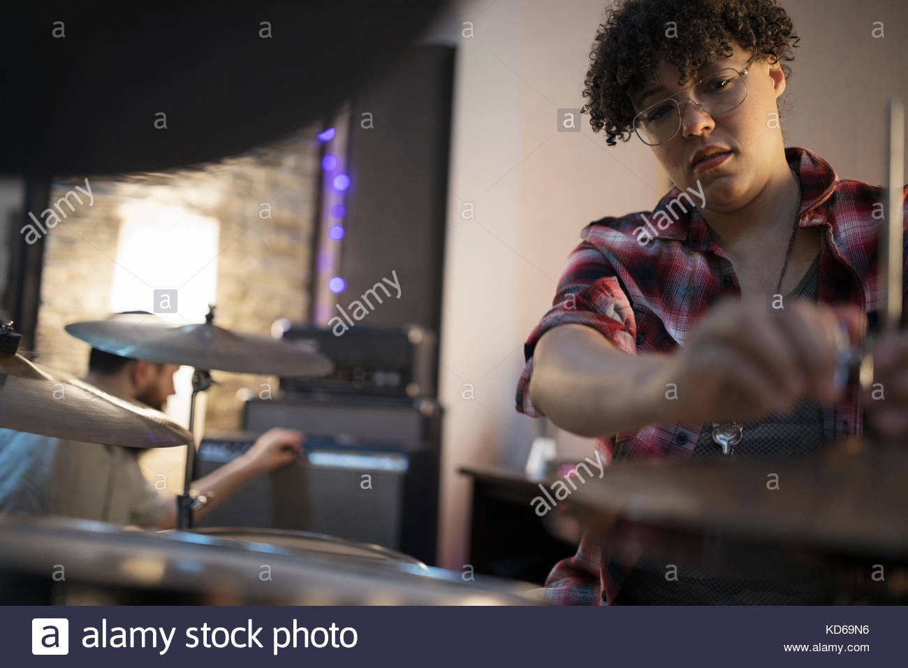Female drummer playing in recording studio - Stock Image