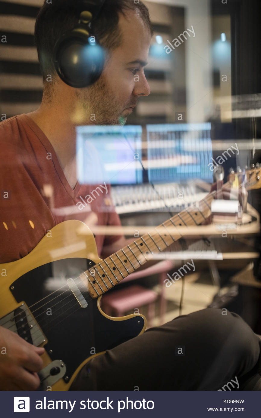 Focused male guitarist with headphones playing in recording studio - Stock Image