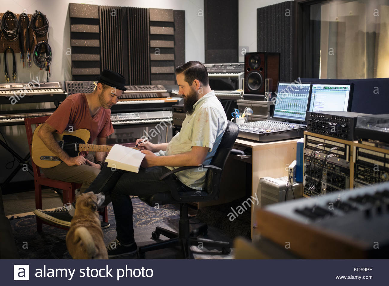 Male music producer and guitarist meeting in recording studio - Stock Image
