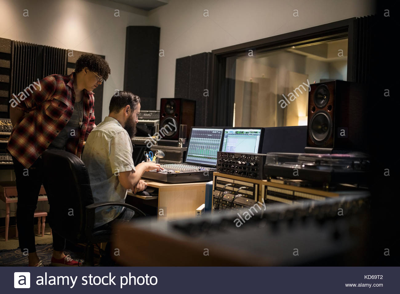 Music producers working at sound mixer in recording studio Stock Photo