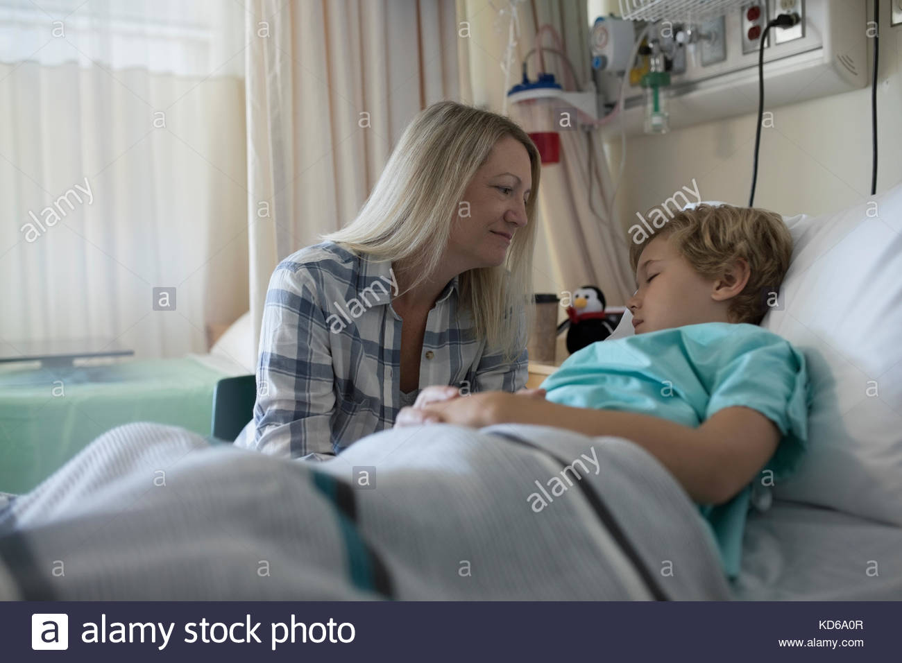 Affectionate mother watching sleeping son boy patient sleeping in hospital bed - Stock Image