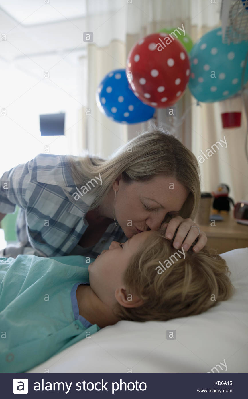 Affectionate mother kissing forehead of sleeping son boy patient sleeping in hospital bed - Stock Image
